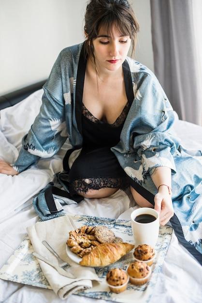 Belle femme assise sur le lit, prenant son petit déjeuner Photo gratuit