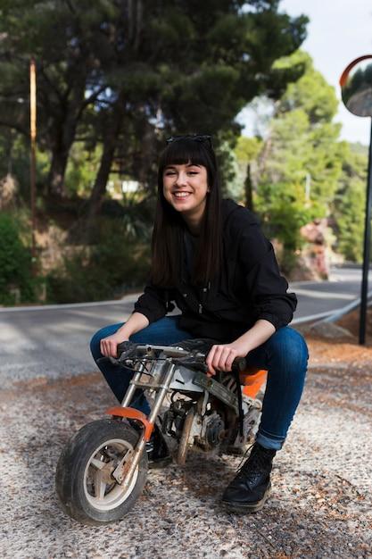 Belle femme assise sur une petite moto Photo gratuit