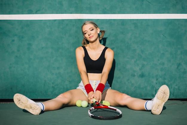 Belle femme assise sur un terrain de tennis Photo gratuit