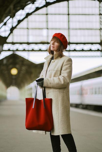 Belle Femme Attend Le Train Sur La Gare. Fille Voyage Léger. Femme D'âge Moyen Photo Premium