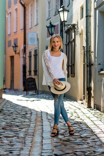 Une belle femme au chapeau léger, aux longs cheveux blonds, à une blouse blanche et à des jeaans bleus au milieu de la vieille ville Photo Premium