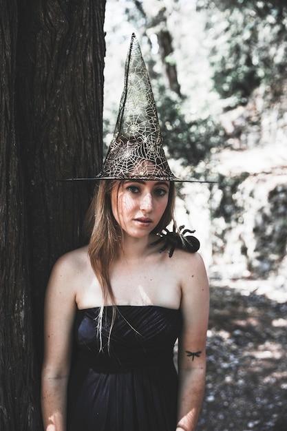 Belle Femme Au Chapeau De Sorcière Debout Près D'un Arbre Et Regardant La Caméra Photo gratuit