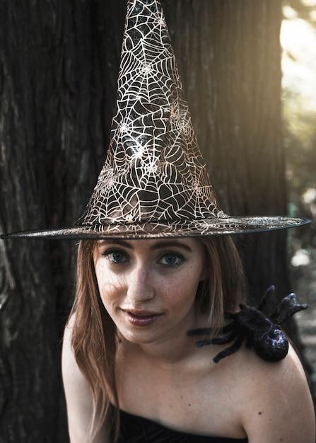 Belle Femme Au Chapeau De Sorcière Regardant La Caméra Avec Une Araignée Décorative Assis Sur L'épaule Photo gratuit