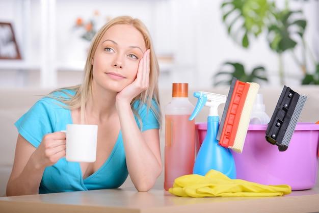 Belle femme au foyer, buvant du thé pendant le nettoyage à la maison Photo Premium