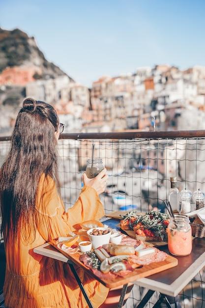 Belle femme au petit-déjeuner au café en plein air avec vue imprenable à cinque terre Photo Premium