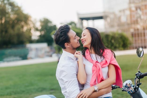 Belle Femme Aux Cheveux Noirs Embrassant Joyeusement Son Mari En Bonne Journée D'été Sur Fond De Nature Photo gratuit