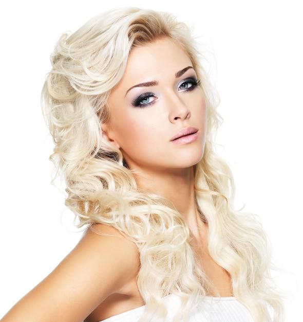 Belle Femme Aux Longs Cheveux Blonds Bouclés. Portrait De Mannequin Avec Un Maquillage Lumineux. Isolé Sur Blanc Photo gratuit