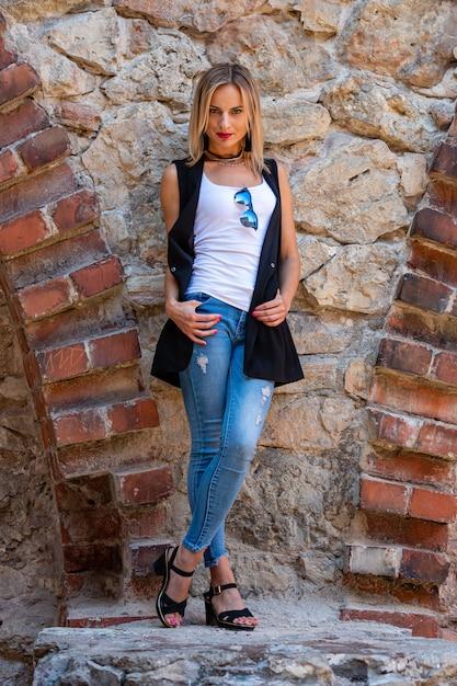 Une belle femme aux longs cheveux blonds, un chemisier blanc et des jeaans bleus près du mur de pierre de la vieille ville Photo Premium