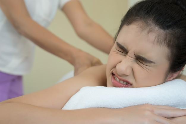 Belle Femme Ayant Massage Du Dos Et Se Sentir Visiblement Bien. Photo gratuit