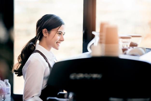 Belle femme barista en uniforme debout et travaillant avec machine à café. Photo Premium
