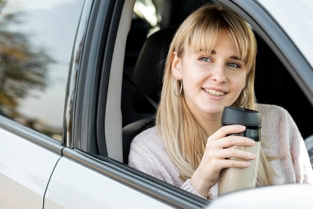 Belle femme blonde assise dans la voiture Photo gratuit
