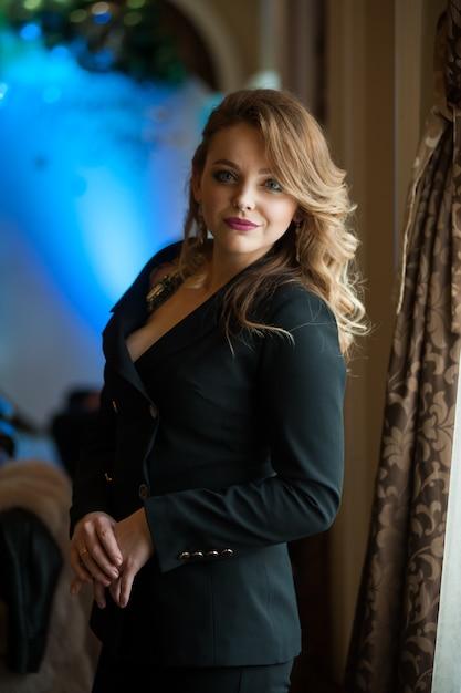 Belle Femme Blonde Aux Cheveux Ondulés Dans Un Costume Noir D'affaires Photo Premium