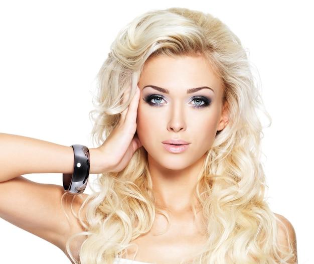 Belle Femme Blonde Aux Longs Cheveux Bouclés Et Maquillage De Style. Fille Posant Sur Un Mur Blanc Photo gratuit