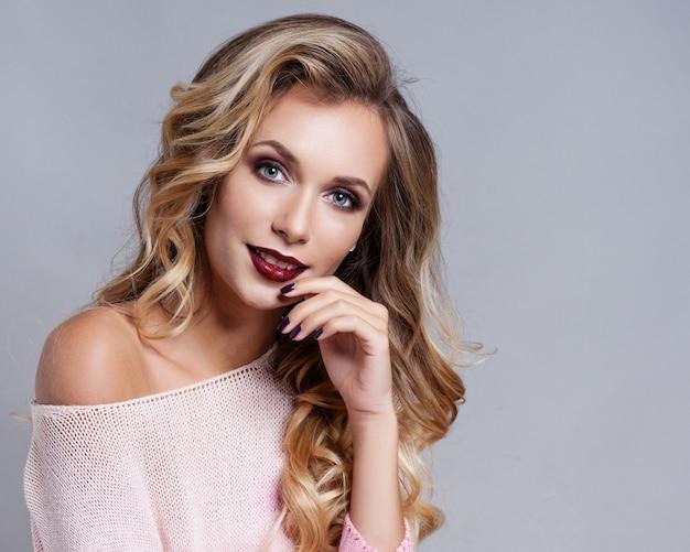 Belle femme blonde aux longs cheveux bouclés Photo Premium