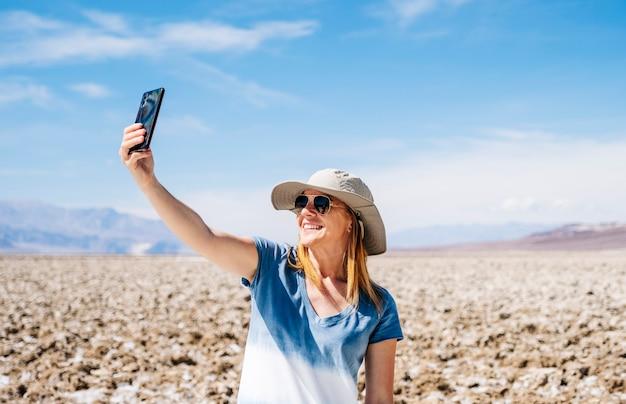 Une Belle Femme Blonde Avec Un Chapeau De Soleil Et Une Robe D'été Bleu Jaune Et Blanc, Prend Une Photo Selfie Avec Le Téléphone Portable Dans Le Désert De Death Valley Par Une Journée Ensoleillée Photo Premium
