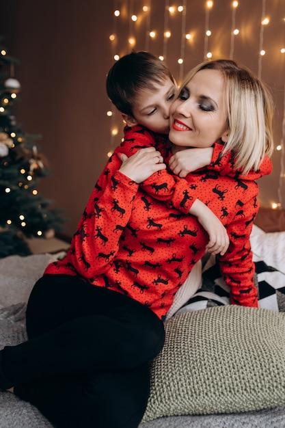 Belle femme blonde embrasse son fils tendre couché sur le lit devant un arbre de noël Photo gratuit