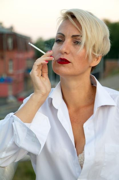 Belle Femme Blonde Mature En Chemise Blanche Fume Une Cigarette Blanche à L'extérieur En Ville à L'été Photo Premium
