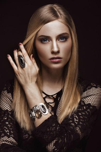 Belle Femme Blonde Avec Une Peau Et Des Cheveux Sains, Manucure Rouge, Qui Pose En Studio Photo Premium