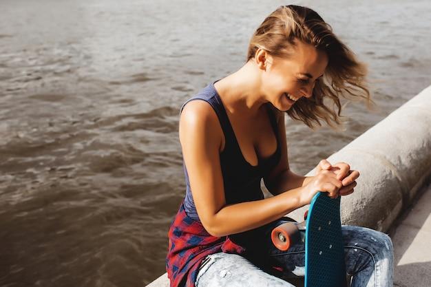 Belle femme blonde posant avec une planche à roulettes Photo gratuit