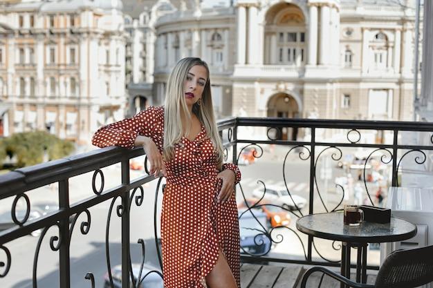 Belle Femme Blonde Vêtue D'une Longue Robe à Pois Rouge Est Debout Sur La Terrasse Près De La Table Basse Avec Vue Sur La Rue De La Ville Avec De Vieux Bâtiments Architecturaux Photo gratuit