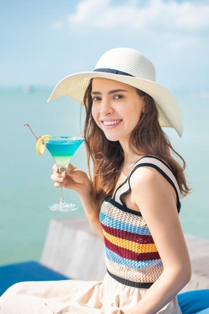Belle femme boit un verre de glace à la plage, concept de l'été Photo Premium
