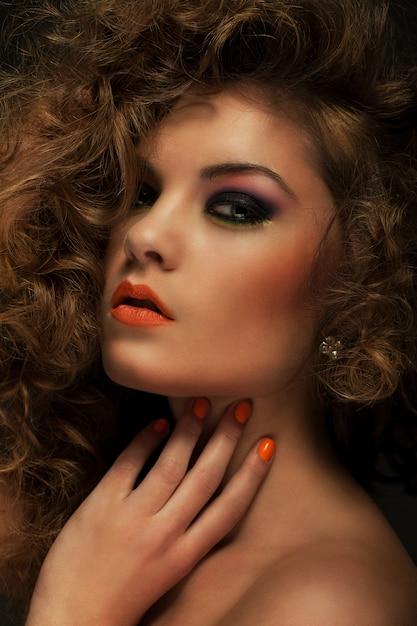Belle femme avec des boucles et du maquillage Photo gratuit