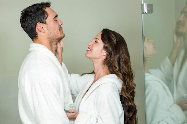 Belle femme brune appliquant une crème hydratante sur le visage de l'homme Photo Premium