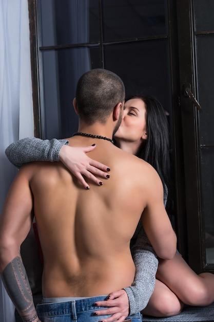 Belle Femme Brune Dans Une Robe Tricotée Est Assise Sur Le Rebord De La Fenêtre Et Embrasse Son Mari Avec La Poitrine Nue Et Les Mains Tatouées Photo Premium
