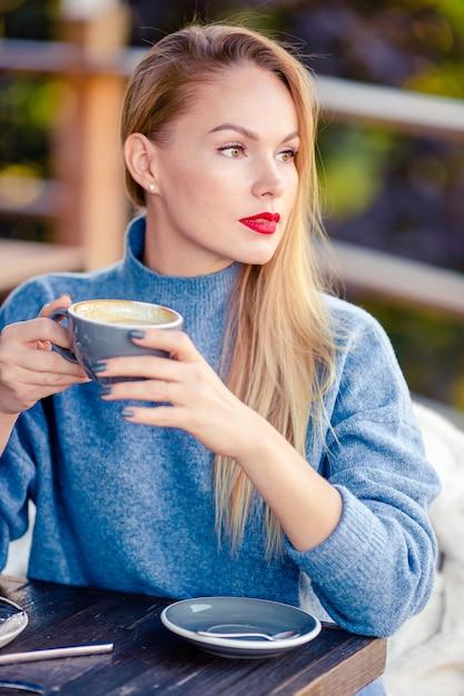 Belle femme buvant du café en automne parc sous le feuillage d'automne Photo Premium