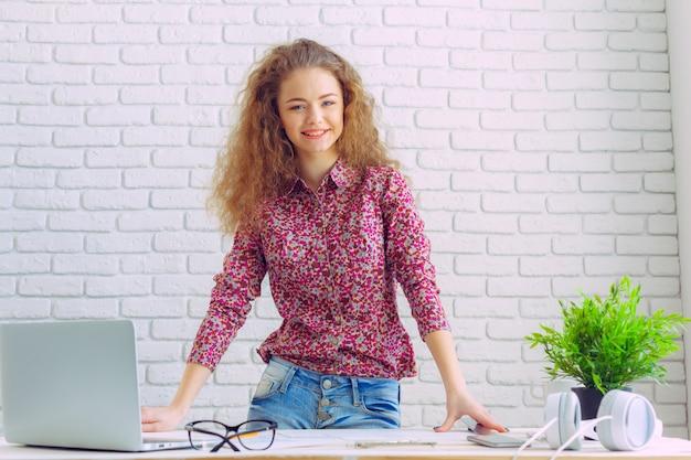 Belle femme caucasienne assise et travaillant sur un ordinateur portable Photo Premium