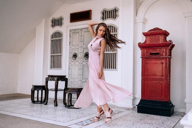 Belle femme caucasienne en robe de soirée rose de luxe et accessoires riches Photo Premium