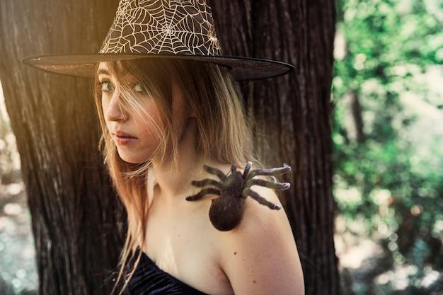 Belle Femme En Chapeau Avec Araignée Décorative Sur L'épaule En Regardant La Caméra Photo gratuit