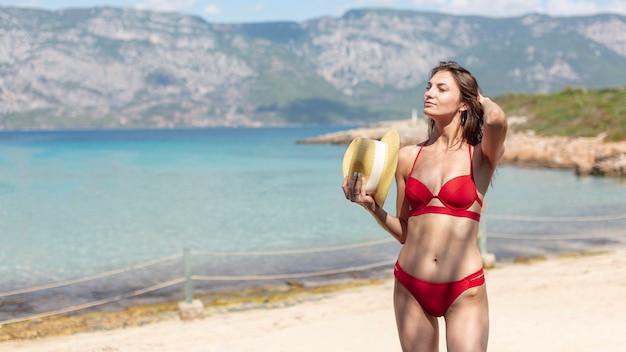 Belle femme avec un chapeau, debout sur la plage Photo gratuit