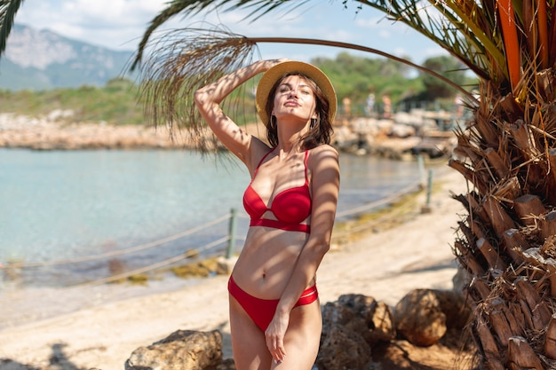 Belle femme avec un chapeau près d'un palmier Photo gratuit