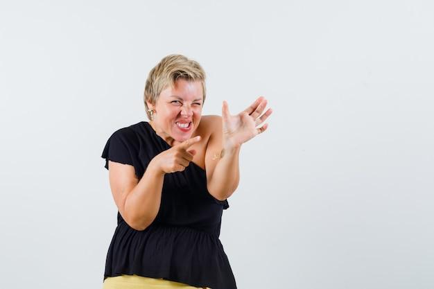 Belle Femme En Chemisier Noir Posant Comme Pointant Sur Le Téléphone Et à La Folie Photo gratuit