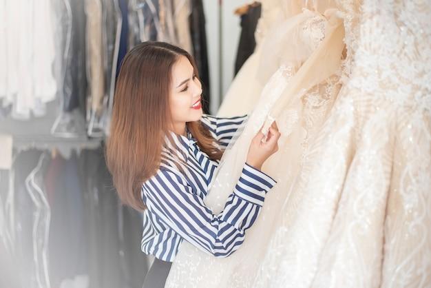 Belle femme cherche robe de mariée dans la boutique de mariage Photo Premium