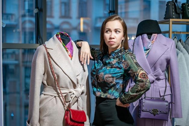 Une belle femme choisit un manteau dans le magasin Photo Premium