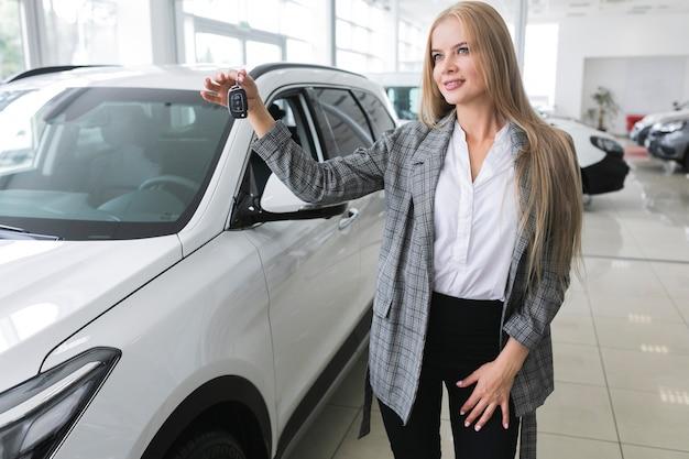 Belle femme avec des clés de voiture à la recherche de suite Photo gratuit