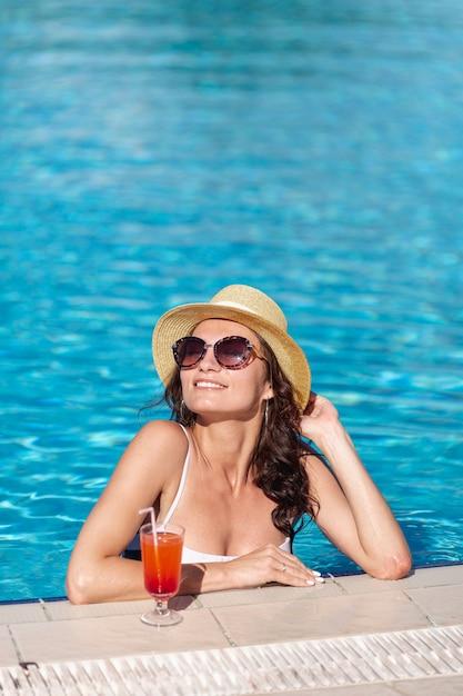 Belle femme avec un cocktail assis dans une piscine Photo gratuit
