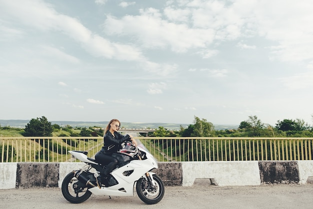 Belle Femme Conduisant Une Moto Sur Une Route Photo gratuit