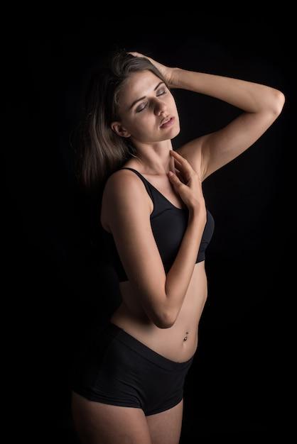 Belle femme avec un corps sain sur fond noir Photo gratuit