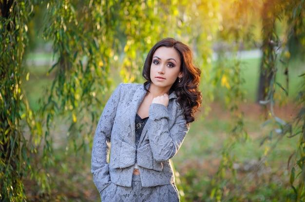 Belle femme en costume gris marchant dans le parc du printemps Photo Premium
