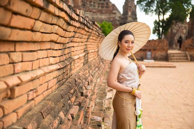 Belle femme en costume traditionnel ancien thaïlandais, portrait à l'ancien temple d'ayutthaya Photo gratuit