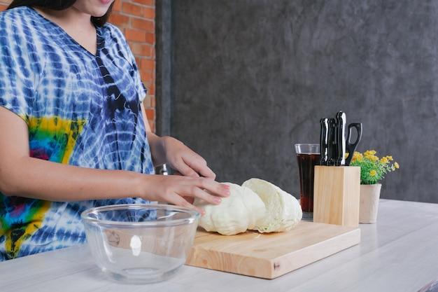 Une belle femme coupe des légumes dans la cuisine à la maison. Photo gratuit