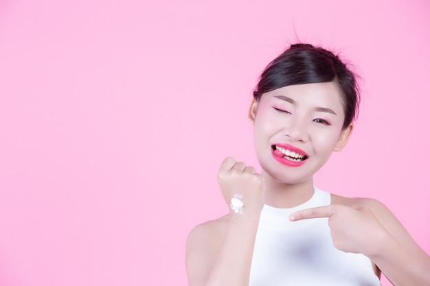 Belle femme avec de la crème sur la peau sur un fond rose. Photo gratuit