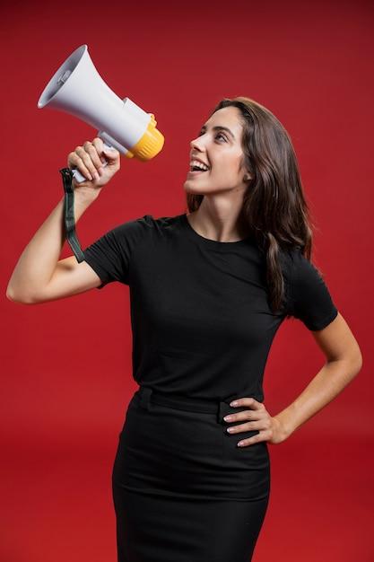 Belle femme criant à travers un mégaphone Photo gratuit