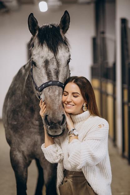 Belle femme dans une écurie à cheval Photo gratuit
