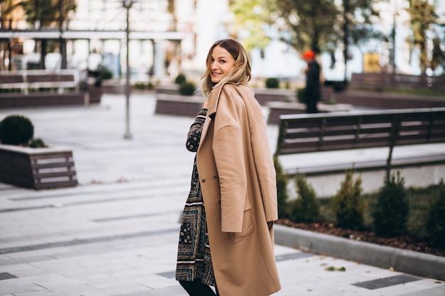 Belle femme dans un manteau beige à l'extérieur dans le parc Photo gratuit