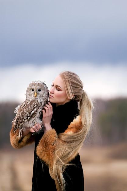 Belle femme dans un manteau de fourrure avec un hibou sur son bras. blonde aux cheveux longs dans la nature tenant un hibou Photo Premium