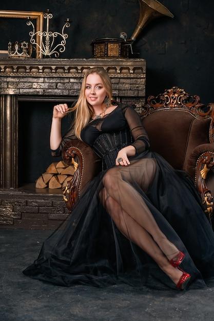 Une belle femme dans une robe noire avec un corset assis sur une chaise en chaussures rouges Photo Premium